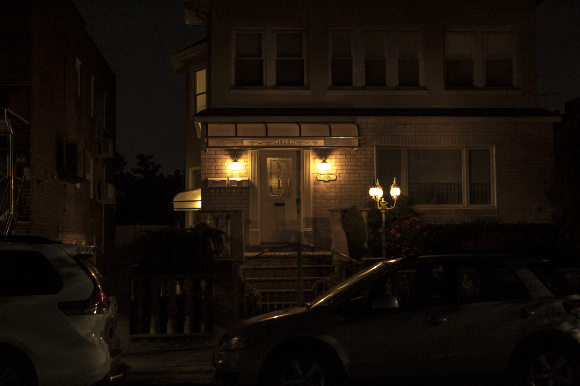 house and cars illuminated by streetlamp