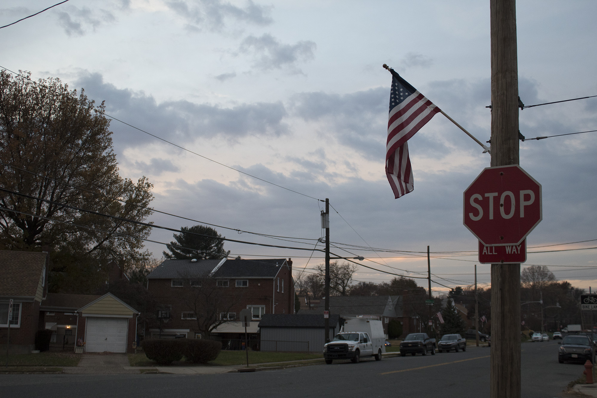 stop sign in suburban neighborhood with american flag hanging from it
